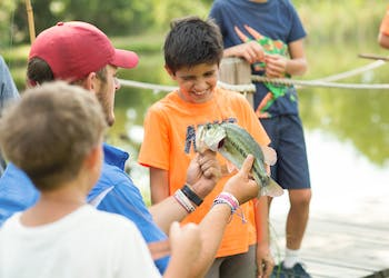 Counselor helps camper fish at the lake.jpg?ixlib=rails 2.1