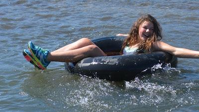 Girl splashes in the river with an inner tube.jpg?ixlib=rails 2.1