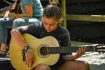 Girl playing guitar at camp.jpg?ixlib=rails 2.1