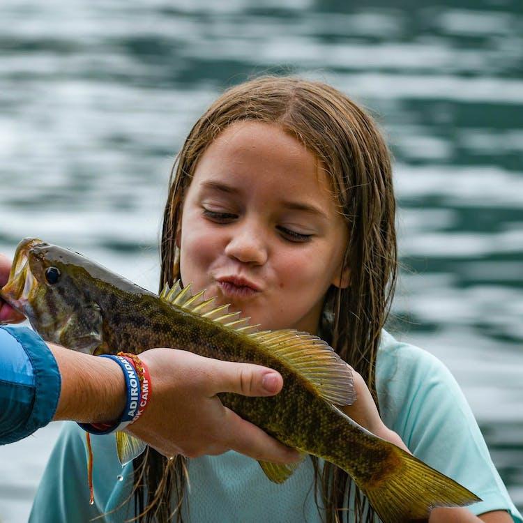 Girl kissing a fish at camp.jpg?ixlib=rails 2.1
