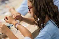 Tying a bracelet.jpg?ixlib=rails 2.1