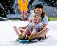 Counselor and camper riding a sled.jpg?ixlib=rails 2.1