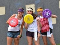 Three girls holding frisbee shields.jpg?ixlib=rails 2.1
