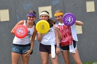 Three girls holding frisbee shields.jpg?ixlib=rails 2.1